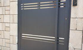 שער אלומיניום מעוצב בשילוב עם חומת אבן משני הצדדים