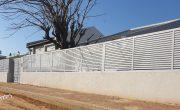 הגבהת חומה עם גדר אלומיניום בצבע לבן ושערי כניסה תואמים