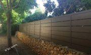 גדר מאלומיניום חום מעל חומת אבן